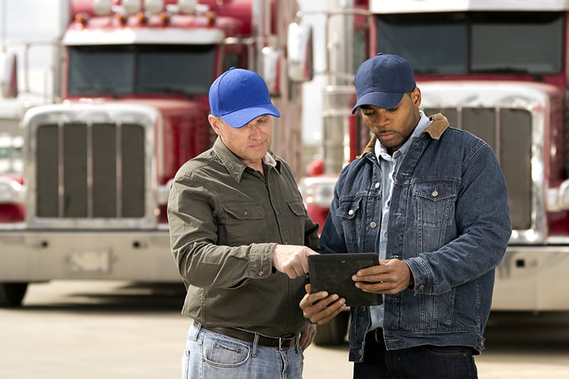 transportation employees pointing at a tablet with two trucks in the background