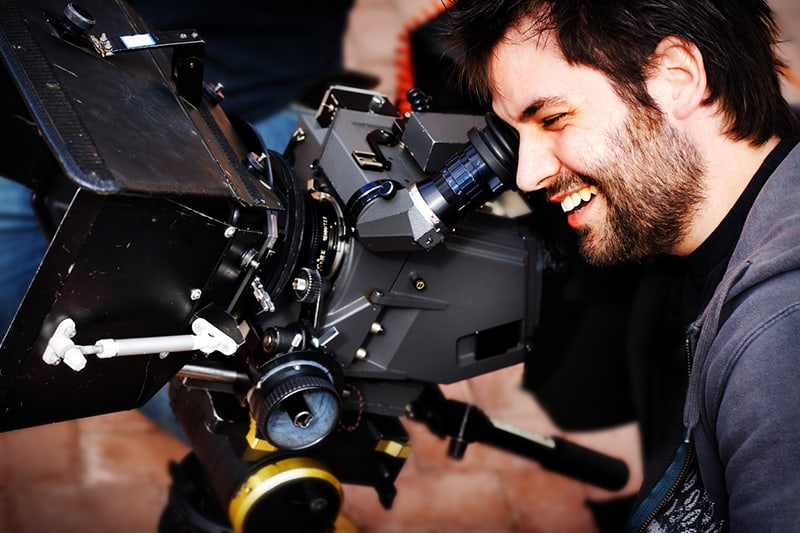 A bearded man looks excitedly into a video camera viewfinder