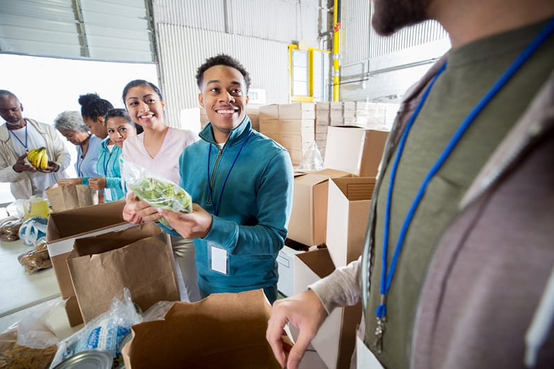 Volunteers smile as they pack food donations into paper bags