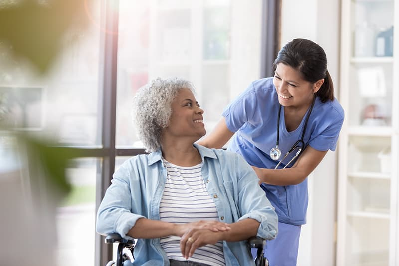 Smiling nurse and senior African American female patient look at one another. The nurse is pushing the woman in a wheelchair.