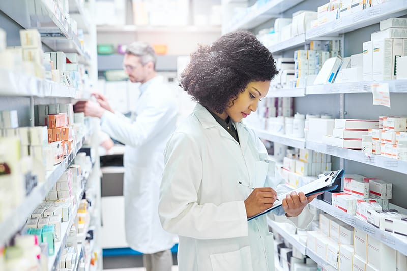 Shot of a young woman doing inventory in a pharmacy with her colleague in the background