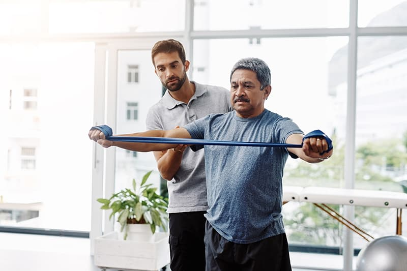 Cropped shot of a young male physiotherapist helping a mature male patient with movement exercises at a clinic